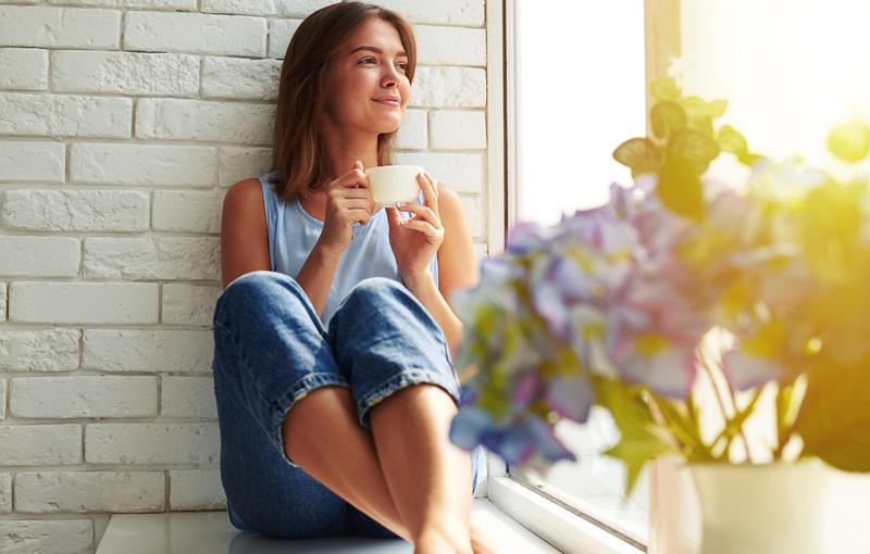 マグカップを持った女性が窓際で微笑んでいる