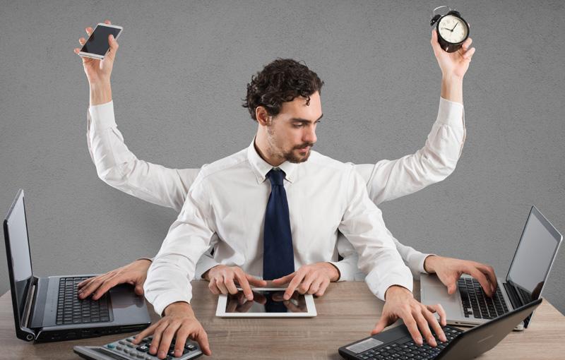 男性が複数のパソコンに向ってマルチタスクをこなしている様子