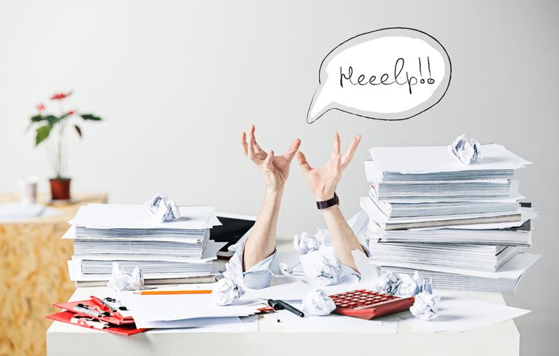 デスクの書類の山に埋もれて助けを求めているビジネスマン