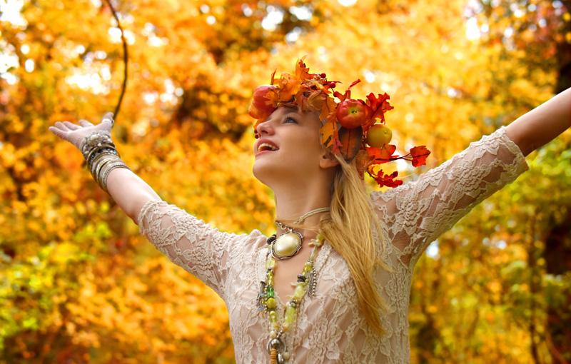 紅葉のなかもみじの髪飾りをつけて腕を広げる女性