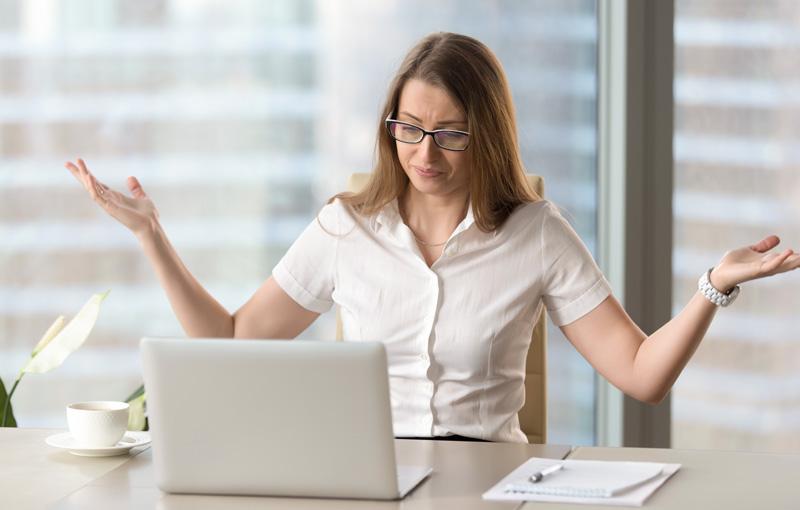 眼鏡をかけた女性がデスクでイライラしながら両手を上げている