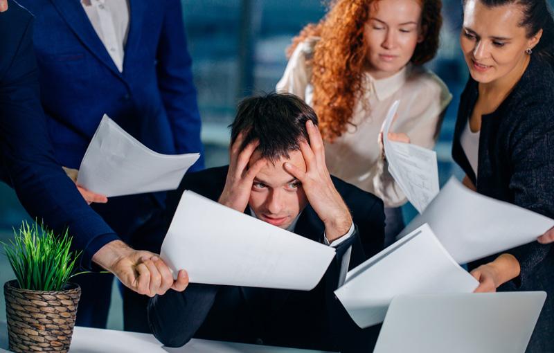 同僚に仕事を頼まれて頭を抱えている男性