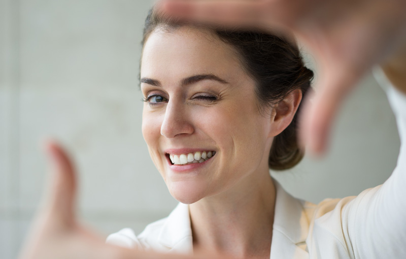 手で構図を確かめている笑顔の女性