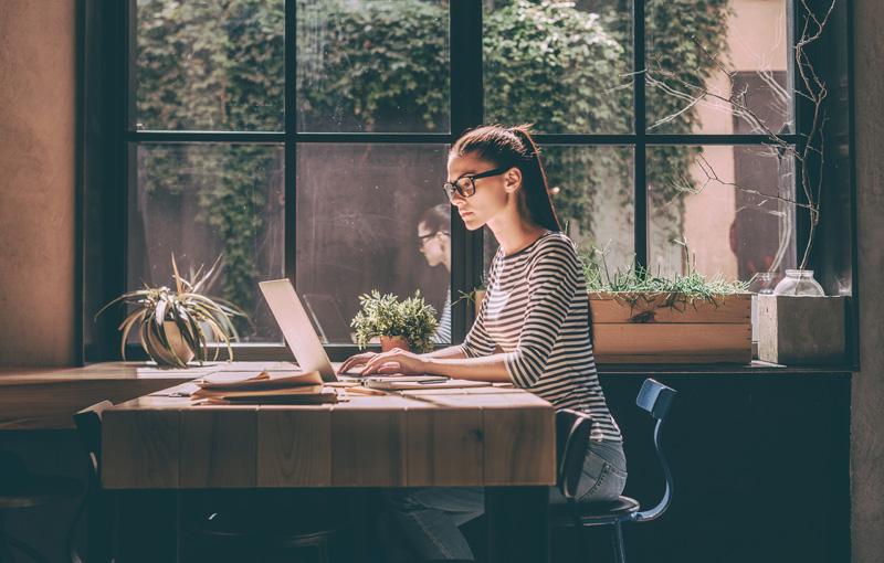 窓際のデスクでパソコン作業に集中しているメガネの女性