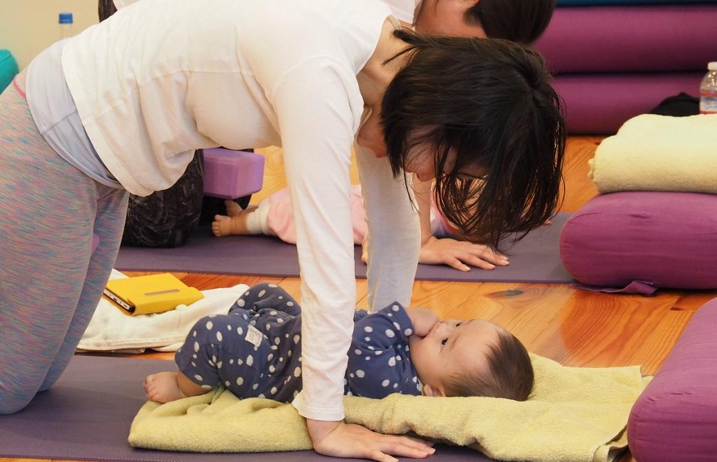 赤ちゃんをブランケットの上に寝かせて四つん這いで見つめるお母さん:産後ヨガクラス