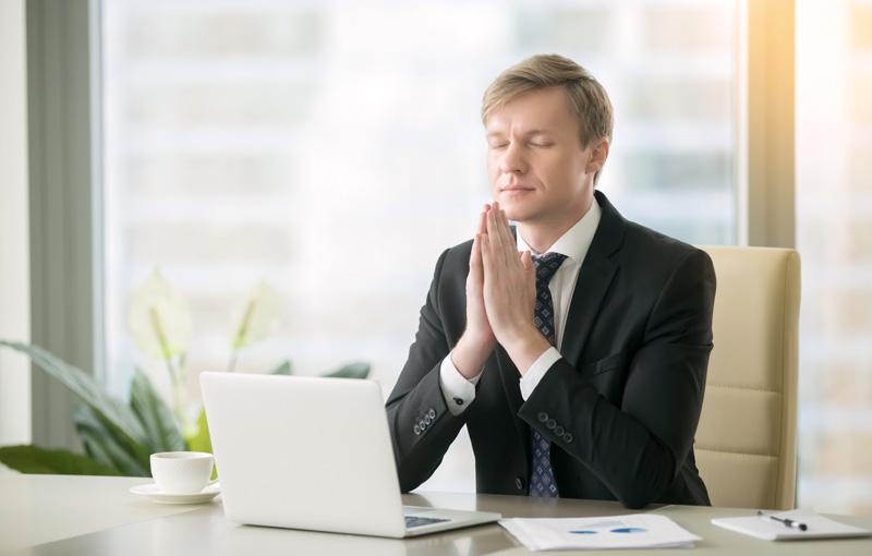 オフィスで瞑想を行うスーツ姿の男性