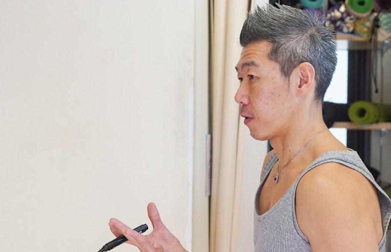 ヨガウェアを着た中島正明先生が生徒に説明している、横向きで写っているvvvvvvvv