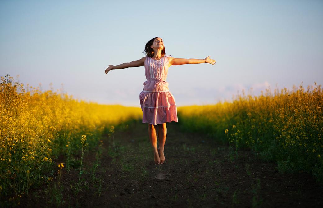 草原で両手を広げてジャンプしている笑顔の女性