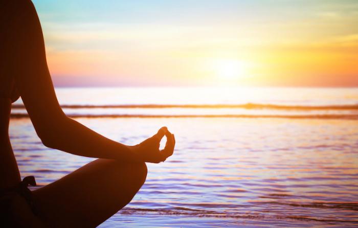 ビーチで座りながら瞑想をしている人の影が夕暮れの太陽に照らされている