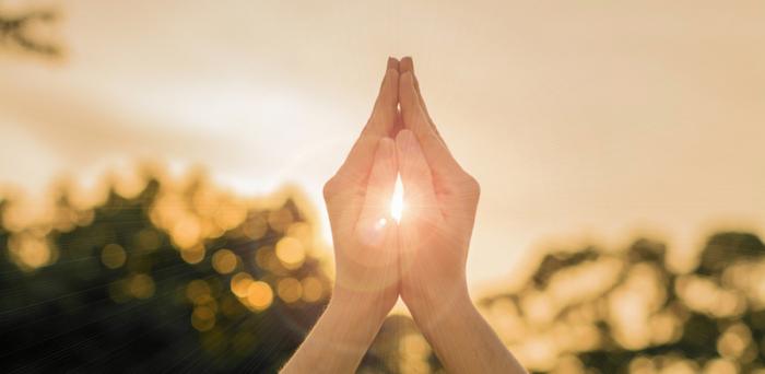合掌している手の間から光が溢れている