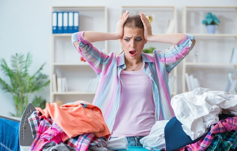 たくさんの服を前に頭を抱える女性