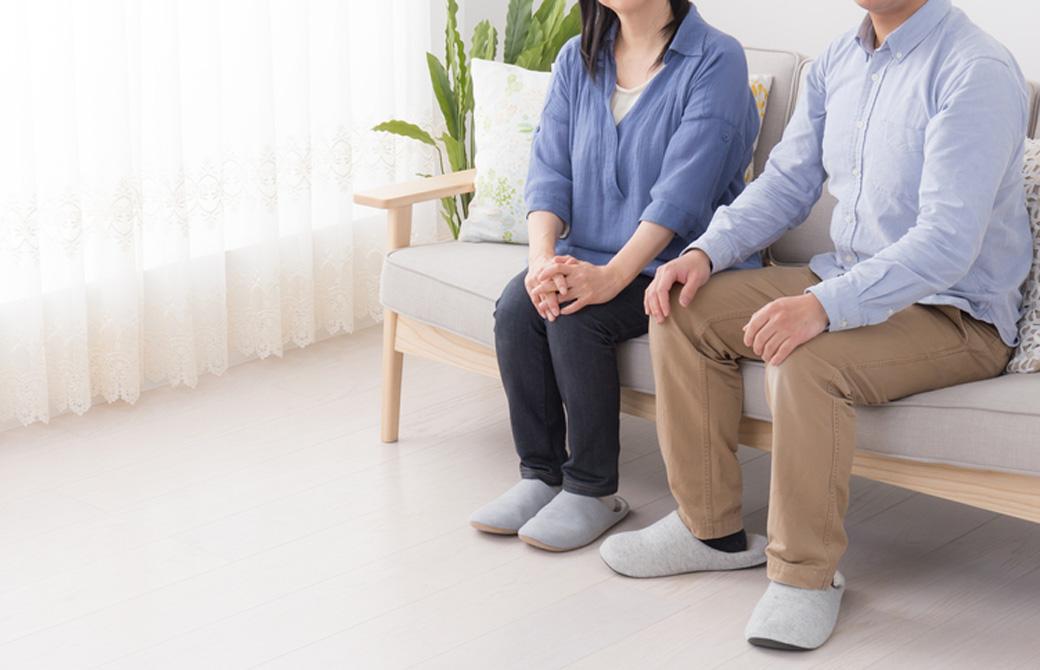 シニア世代の男女がソファに座っている